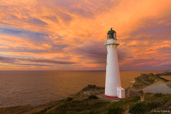 The rising sun illuminates the clouds behind Castlepoint Lighthouse on the North Island of New Zealand.