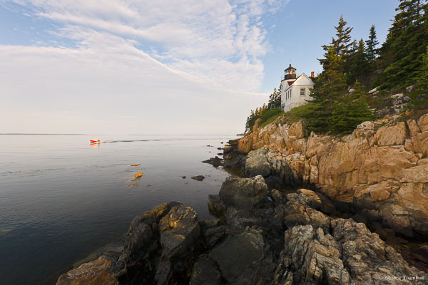 A bright red lobster boat cruises by the Bass Harbor Head Light shortly after sunrise in Acadia National Park, Maine.