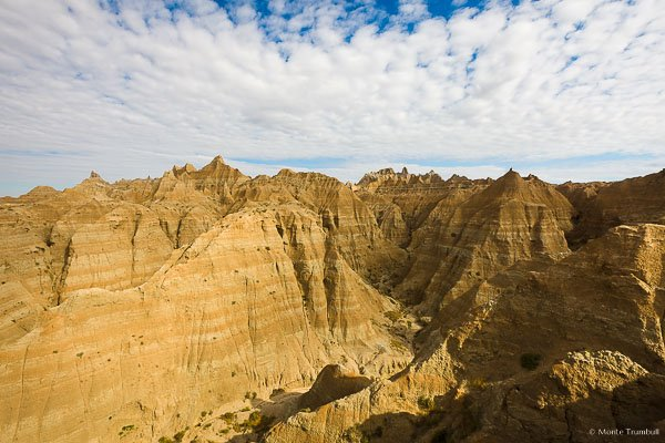 Patches of sunlight illuminate the layered rock spires in Badlands National Park, South Dakota.
