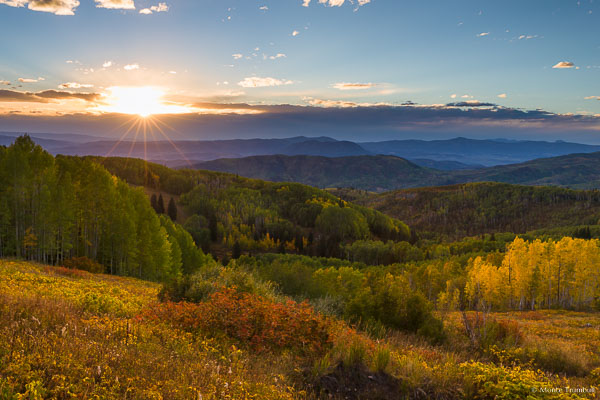 The sun sets through distant clouds beyond a golden hillside and a valley dotted with vibrant fall color outside of Steamboat Springs, Colorado.