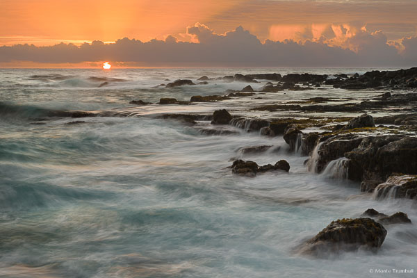 The orange ball of the sun radiates shafts of light skyward through the clouds as it rises over the horizon off a rocky shoreline pounded by waves on the east coast of Kauai, Hawaii.